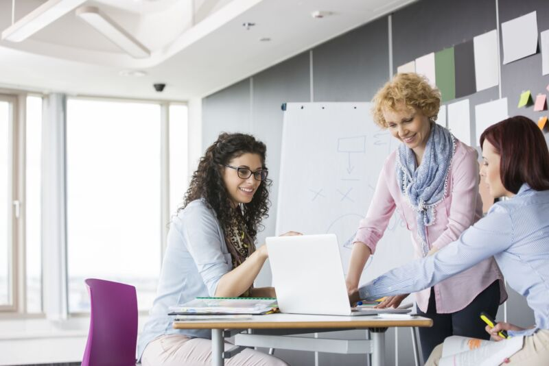 Businesswomen Working Together In Creative Office - Achieve More